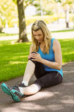 Fit blonde touching her injured knee on path Stock Photos