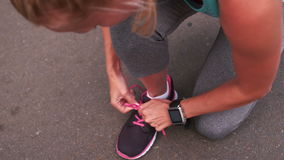Fit blonde tying her shoe lace stock video