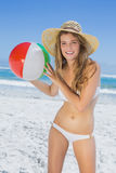 Fit blonde in white bikini and straw hat holding beach ball Royalty Free Stock Photography