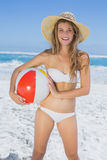 Fit blonde in white bikini and straw hat holding beach ball Royalty Free Stock Images