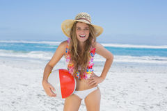 Fit blonde in white bikini and straw hat holding beach ball Royalty Free Stock Photo