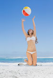 Fit blonde in white bikini throwing beach ball Royalty Free Stock Photography