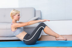 Fit blonde woman doing sit ups Stock Images