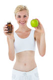 Fit blonde woman holding medicine and green apple. On white background Stock Photography