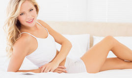 Fit blonde woman lying on bed smiling at camera Stock Photography