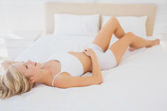 Fit blonde woman relaxing on bed Stock Photo