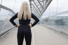 Fit blonde woman runner standing on bridge in modern looking city. Back of fit blonde woman runner standing on bridge in modern looking city royalty free stock image