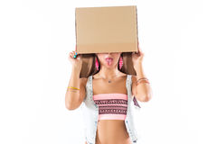 Fit blonde woman standing, holding cardboard box over head, hiding face, posing, having fun. Royalty Free Stock Photography