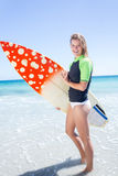 Fit blonde woman standing in the water and holding surfboard Stock Photography