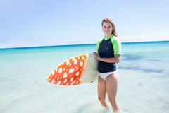 Fit blonde woman standing in the water and holding surfboard Royalty Free Stock Images