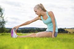 Fit blonde woman stretching outdoor on the grass Stock Photo