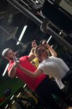 Fit woman working out in gym with personal coach. Fit blonde women working out in gym with assistance of personal coach. Young male trainer with female client Royalty Free Stock Photo