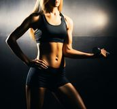 Fit body of beautiful, healthy and sporty girl with a dumbbells. Slim woman posing in sportswear. Stock Photography