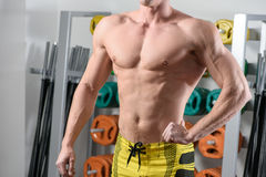 Fit bodybuilder posing in gym. Without head Stock Photo