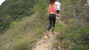 Fit boy and girl jogging on mountain track. Woman and man run in nature stock video footage