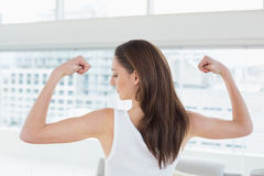 Fit brown haired woman flexing muscles in fitness studio Stock Image