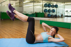 Fit brunette doing sit ups in fitness studio Stock Images