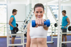 Fit brunette exercising with blue dumbbells Stock Image