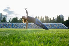 Fit brunette girl in sport clothing doing side plank exercise outdoor at the stadium royalty free stock photography