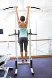 Fit brunette hanging from bars. At the gym Royalty Free Stock Image