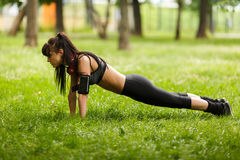 Fit brunette in headphones doing plank core exercise on grass royalty free stock photo