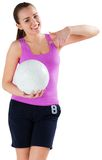Fit brunette holding ball pointing at it Royalty Free Stock Image