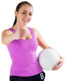 Fit brunette holding ball showing thumbs up Stock Photos
