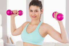 Fit brunette holding dumbbells smiling at camera Stock Photos