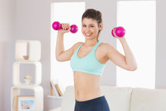 Fit brunette holding dumbbells smiling at camera Royalty Free Stock Photo