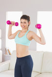 Fit brunette holding dumbbells smiling at camera Royalty Free Stock Images