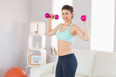 Fit brunette holding dumbbells smiling at camera Royalty Free Stock Photography