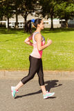 Fit brunette jogging on path Stock Images