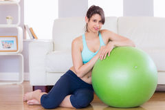 Fit brunette leaning on exercise ball smiling at camera Royalty Free Stock Photography