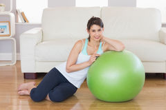 Fit brunette leaning on exercise ball smiling at camera Stock Photography