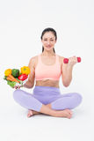 Fit brunette lifting dumbbell and holding bowl of salad Royalty Free Stock Images
