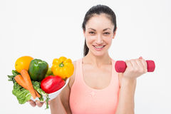 Fit brunette lifting dumbbell and holding bowl of salad Stock Photos