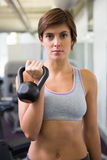 Fit brunette lifting kettlebell looking at camera Royalty Free Stock Photography