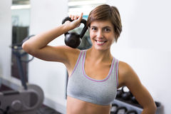 Fit brunette lifting kettlebell smiling at camera Royalty Free Stock Photo