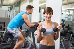 Fit brunette lifting weights smiling at camera Stock Photography