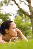 Fit brunette lying and thinking on grass Royalty Free Stock Images