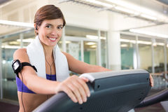 Fit brunette running on the treadmill listening to music Royalty Free Stock Photo