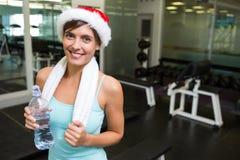 Fit brunette in santa hat smiling at camera Stock Photo