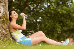 Fit brunette sitting against tree drinking water Stock Image