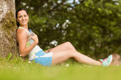 Fit brunette sitting against a tree holding her bottle Stock Photo
