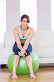 Fit brunette sitting on exercise ball smiling at camera Stock Photo