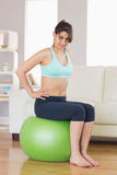 Fit brunette sitting on exercise ball smiling at camera Royalty Free Stock Photo