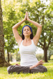 Fit brunette sitting in lotus pose in the park Stock Image