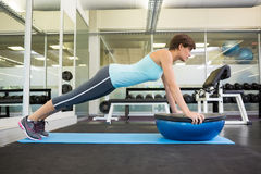 Fit brunette using bosu ball in plank position Stock Images