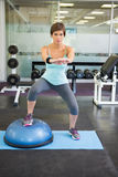Fit brunette using bosu ball for squats Stock Photo
