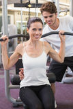 Fit brunette using weights machine for arms with trainer helping Royalty Free Stock Photography